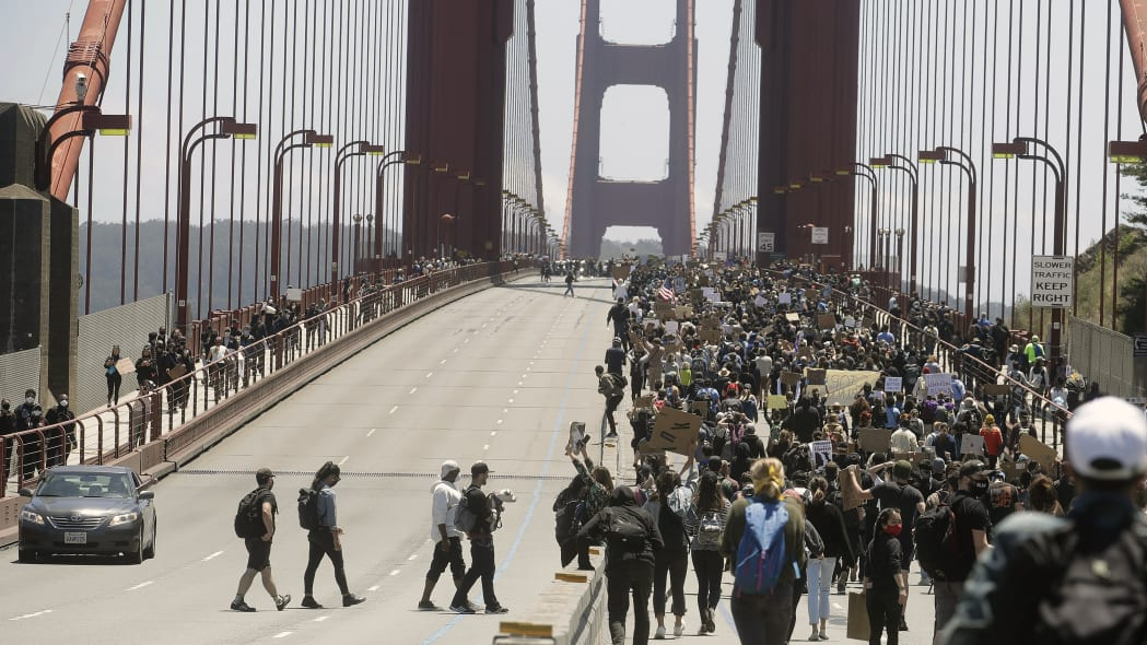 People cross over lanes to join others marching south on the Golden Gate Bridge in San Francisco, Saturday, June 6, 2020, at a protest over the Memorial Day death of George Floyd. Floyd died May 25 after being restrained by Minneapolis police. (AP Photo/Jeff Chiu)