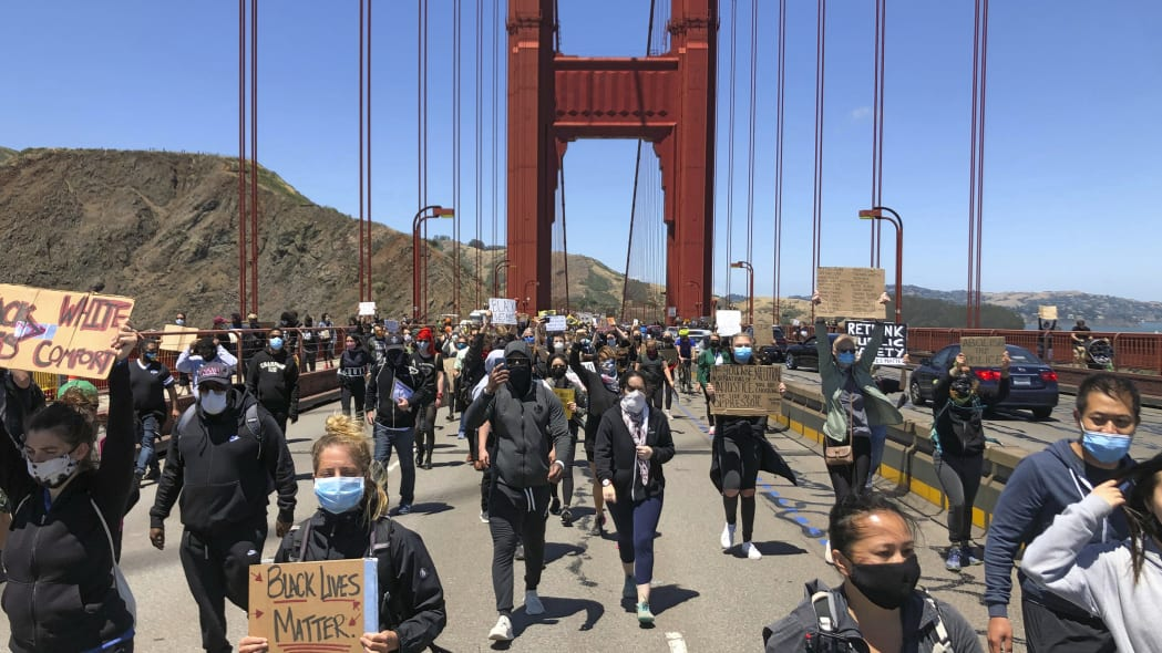 Dozens of people march across the Golden Gate Bridge in support of the Black Lives Matter movement in San Francisco Saturday, June 6, 2020. People are protesting the death of George Floyd, who died after he was restrained by Minneapolis police on May 25 in Minnesota. (AP Photo/Jeff Chiu)