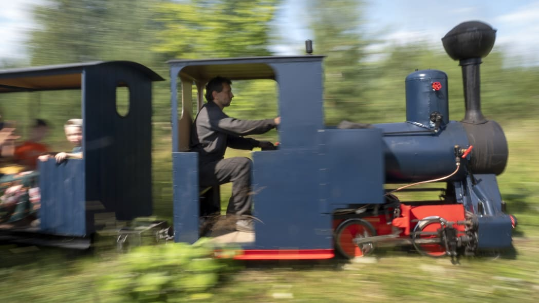 Sergei Terekhov drives a miniature steam train traveling along Pavel Chilin's personal railway in Ulyanovka village outside St. Petersburg, Russia, Sunday, July 19, 2020.  It took Chilin more than 10 years to build a 350-meter-long mini-railway twisting through the grounds of his cottage home about 50 kilometers (some 30 miles) outside St. Petersburg, complete with various branches, dead ends, circuit loops, and even three bridges.(AP Photo/Dmitri Lovetsky)