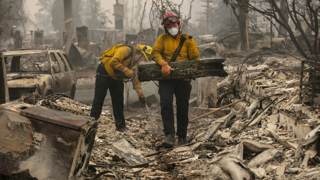 Jackson County District 5 firefighter Captain Aaron Bustard, right, and Andy Buckingham work on a smoldering fire in a burned neighborhood as destructive wildfires devastate the region on Friday, Sept. 11, 2020, in Talent, Ore. (AP Photo/Paula Bronstein)