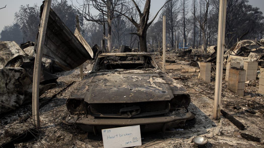"""A sign that reads """"Heart broken"""" is displayed in front of a destroyed vehicle at Coleman Creek Estates mobile home park in Phoenix, Ore., Thursday, Sept. 10, 2020. The area was destroyed when a wildfire swept through on Tuesday, Sept. 8. (AP Photo/Paula Bronstein)"""