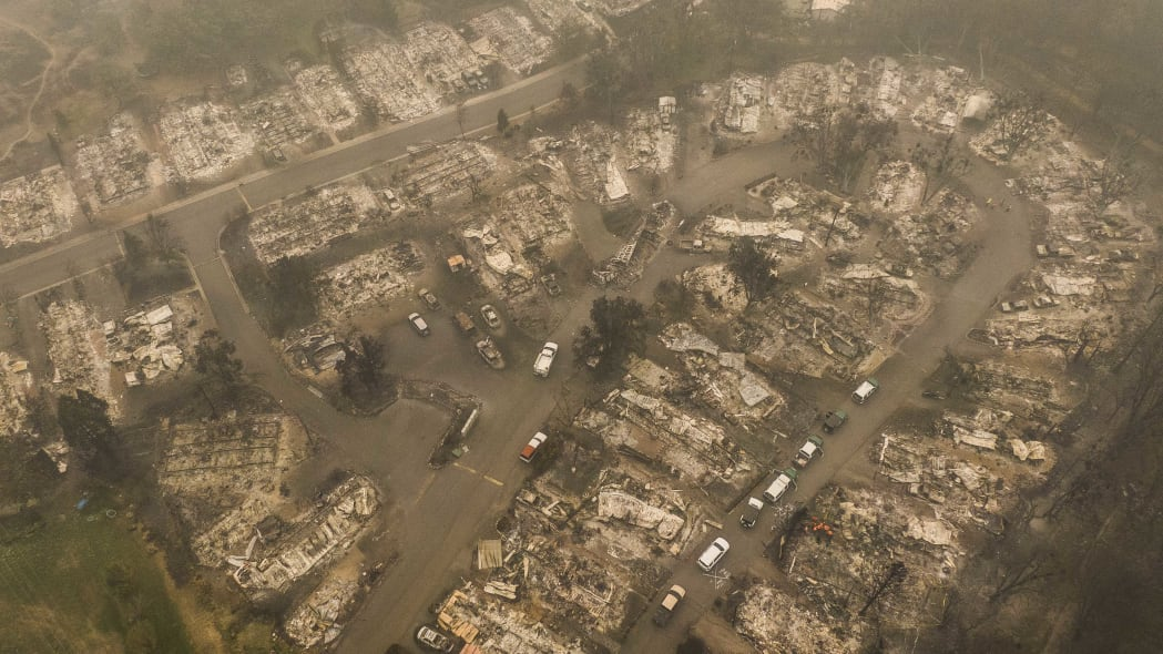 ASHLAND, OR - SEPTEMBER 11: In this aerial view from a drone, search and rescue personnel from the Jackson County Sheriff's Office look for the possible remains of a missing elderly resident in a mobile home park on September 11, 2020 in Ashland, Oregon. Hundreds of homes in Ashland and nearby towns have been lost due to wildfire. (Photo by David Ryder/Getty Images)