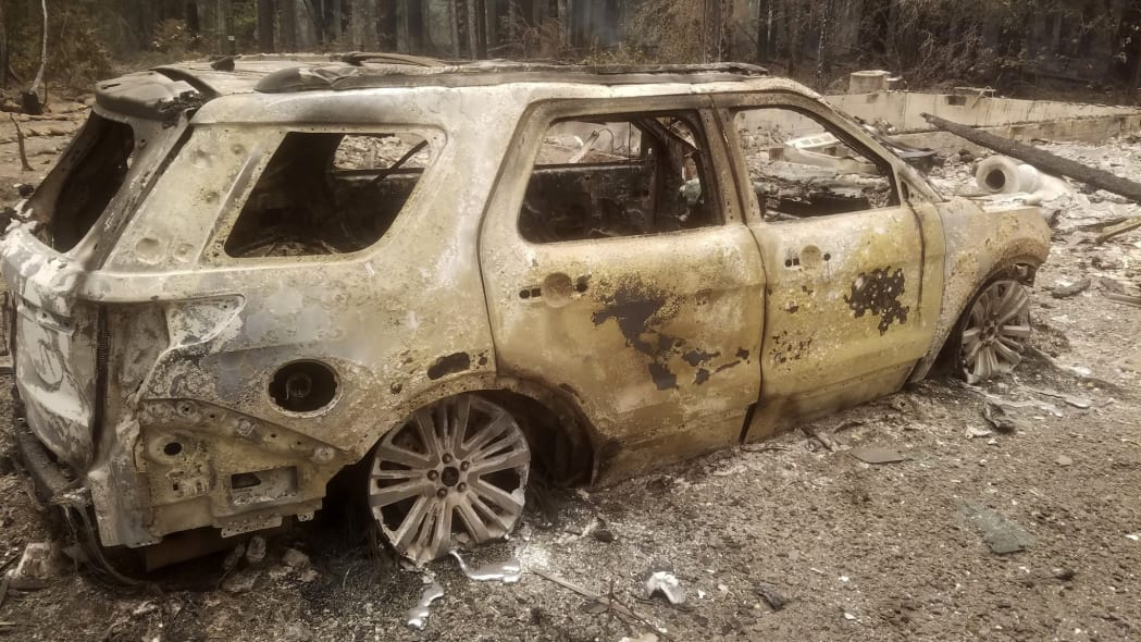 A burned out car is seen near someone's home after the passing of the Holiday Farm fire in McKenzie Bridge, Oregon on September 10, 2020. - California firefighters battled the state's largest ever inferno on September 10, as tens of thousands of people fled blazes up and down the US West Coast and officials warned the death toll could shoot up in coming days. At least eight people have been confirmed dead in the past 24 hours across California, Oregon and Washington, but officials say some areas are still impossible to reach, meaning the number is likely to rise. (Photo by Tyee Burwell / AFP) (Photo by TYEE BURWELL/AFP via Getty Images)