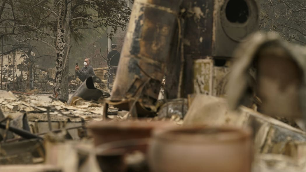 A man takes a picture at a neighborhood destroyed by the Almeda Fire, Friday, Sept. 11, 2020, in Talent, Ore.  (AP Photo/John Locher)