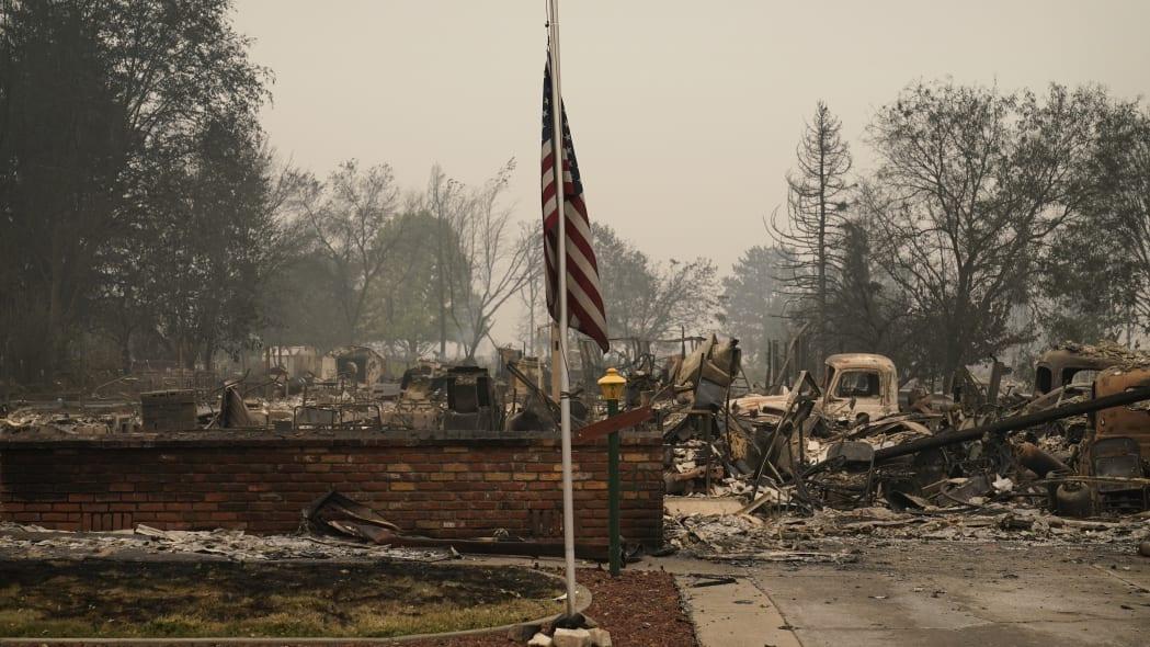 A flag flies in a neighborhood destroyed by the Almeda Fire, Friday, Sept. 11, 2020, in Phoenix, Ore. (AP Photo/John Locher)