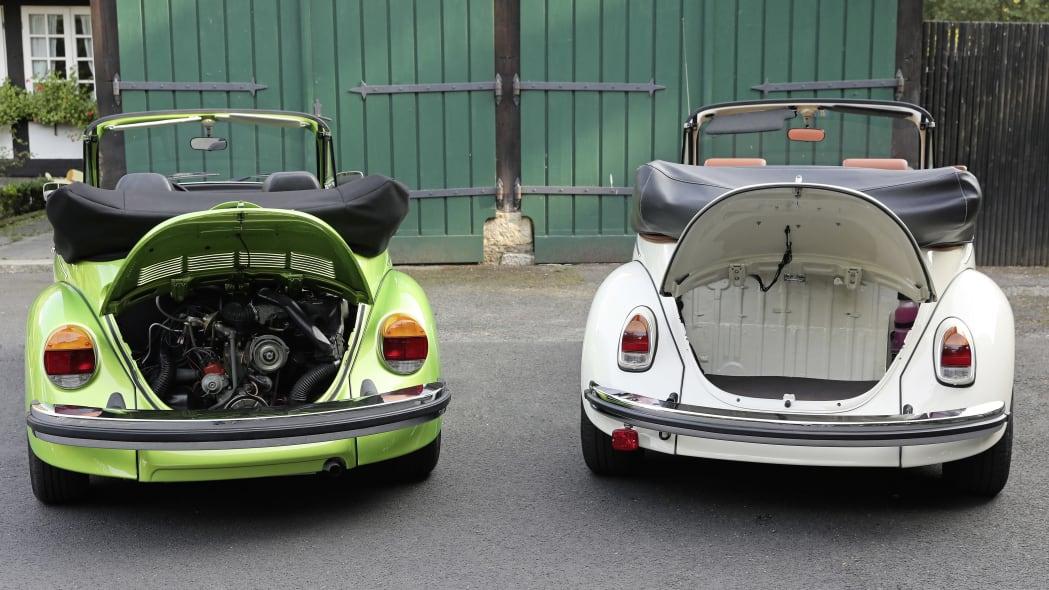 Volkswagen eClassics eBeetle next to a green gas-powered Beetle