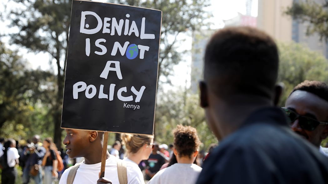 An environmental activist holds a sign as he takes part in the Climate strike protest calling for action on climate change, in Nairobi