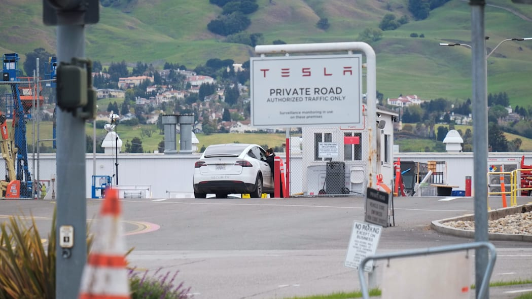 An employee of a Tesla Inc's U.S. vehicle factory is seen at a security gate in Fremont, California