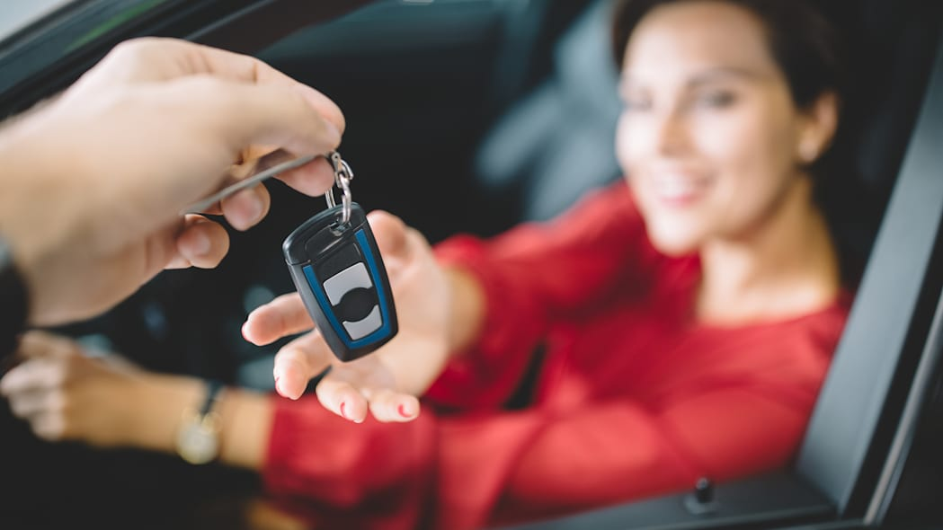 Young woman sitting in new car and taking the keys from the car dealer