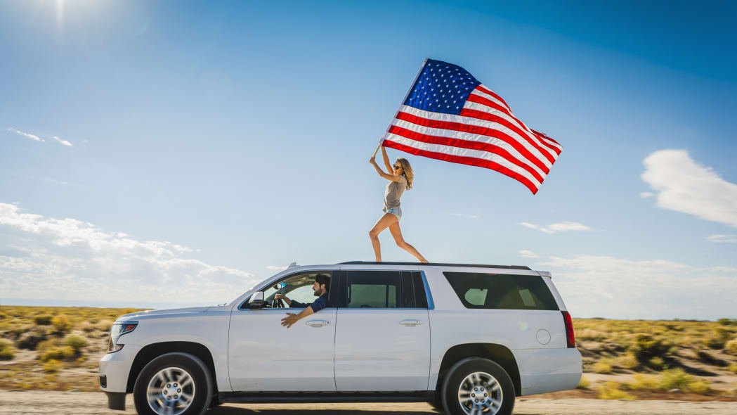 Hispanic woman waving American flag on roof of white SUV