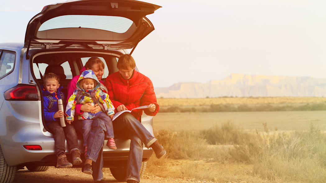 family with two kids travel by car in scenic mountains