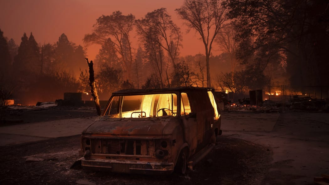 Flames burn inside a van as the Camp Fire tears through Paradise, Calif., on Thursday, Nov. 8, 2018. Tens of thousands of people fled a fast-moving wildfire Thursday in Northern California, some clutching babies and pets as they abandoned vehicles and struck out on foot ahead of the flames that forced the evacuation of an entire town and destroyed hundreds of structures. (AP Photo/Noah Berger)