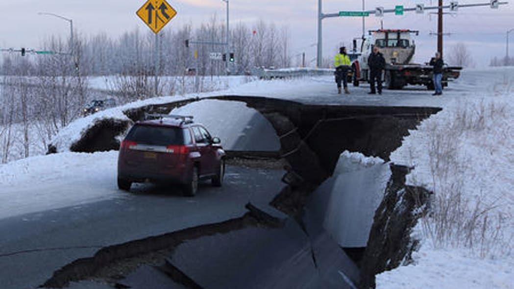 A stranded vehicle lies on a collapsed roadway near the airport after an earthquake in Anchorage