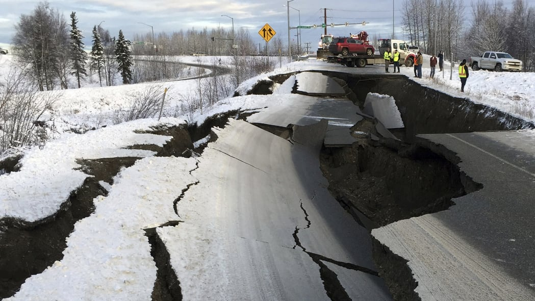 A tow truck holds a car that was pulled from on an off-ramp that collapsed during a morning earthquake on Friday, Nov. 30, 2018, in Anchorage, Alaska. The driver was not injured attempting to exit Minnesota Drive at International Airport Road. Back-to-back earthquakes measuring 7.0 and 5.8 rocked buildings and buckled roads Friday morning in Anchorage, prompting people to run from their offices or seek shelter under office desks, while a tsunami warning had some seeking higher ground.  (AP Photo/Mike Dinneen)