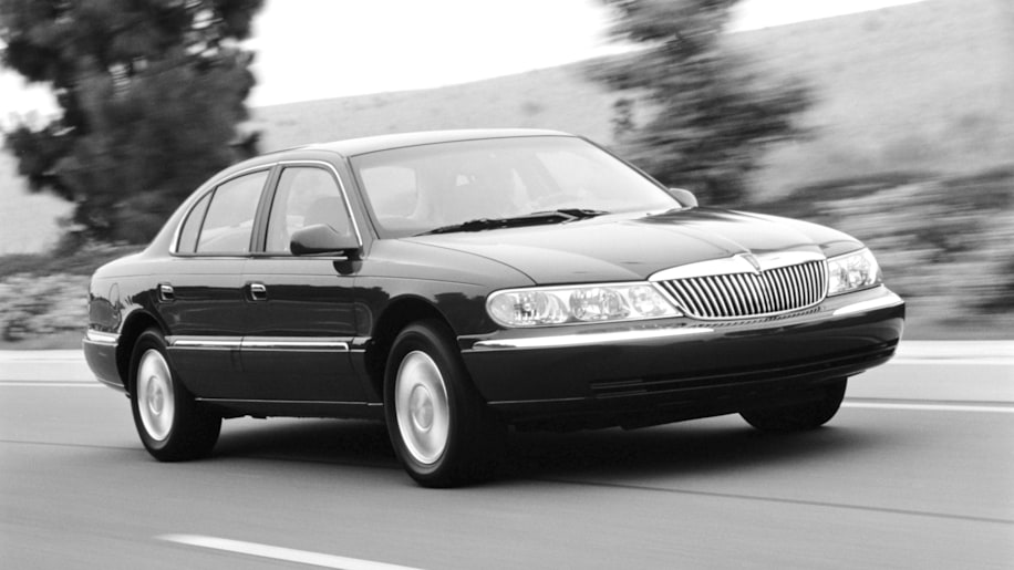 2000 Lincoln Continental black black and white front three quarters driving