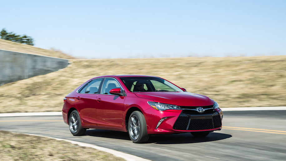 red 2015 toyota camry front three quarters on road