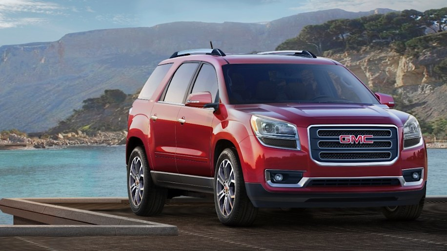 red 2015 gmc acadia front three quarters in front of lake