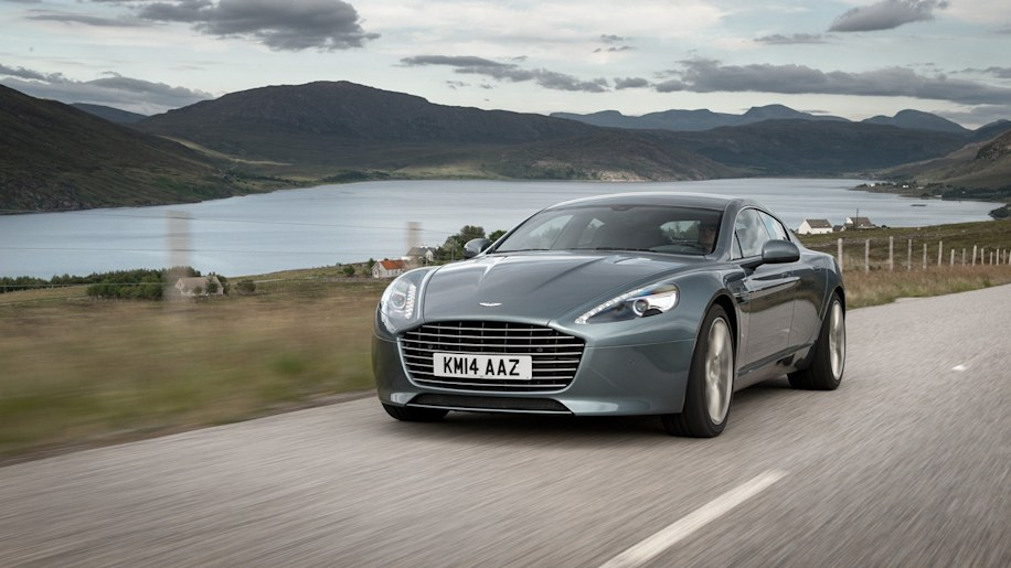 Aston Martin Rapide driving gray lake mountains