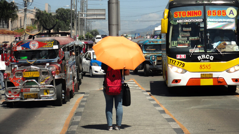 A Filipina waits for a public utility vehicle under the