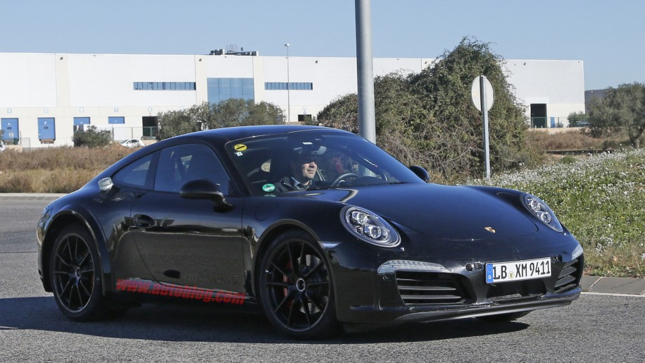 Spy shot of the next-generation 992-model Porsche 911 thought to hide a hybrid powertrain, front three-quarter.
