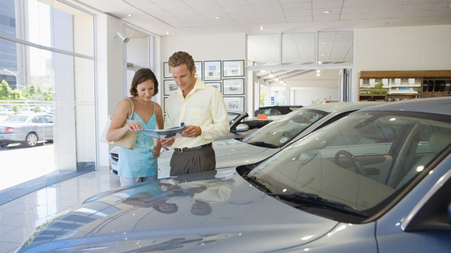 Man and woman looking at brochure in car dealership