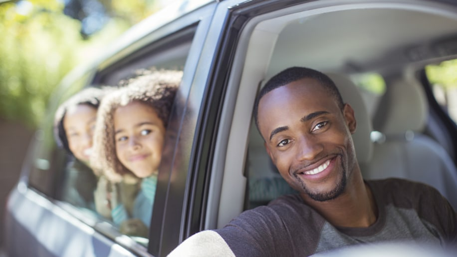 Portrait of happy family leaning out car windows