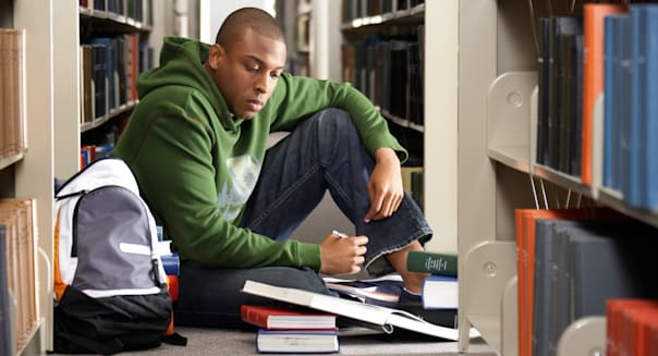 Male college student studying on floor in library --- Image by CorbisStandard Royalty-Free (RF)42-25547587Male college stud
