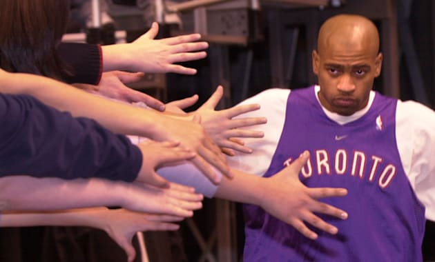 Toronto Raptors' Vince Carter heads to the court in the ACC and is greeted by outstretched hands of fans...