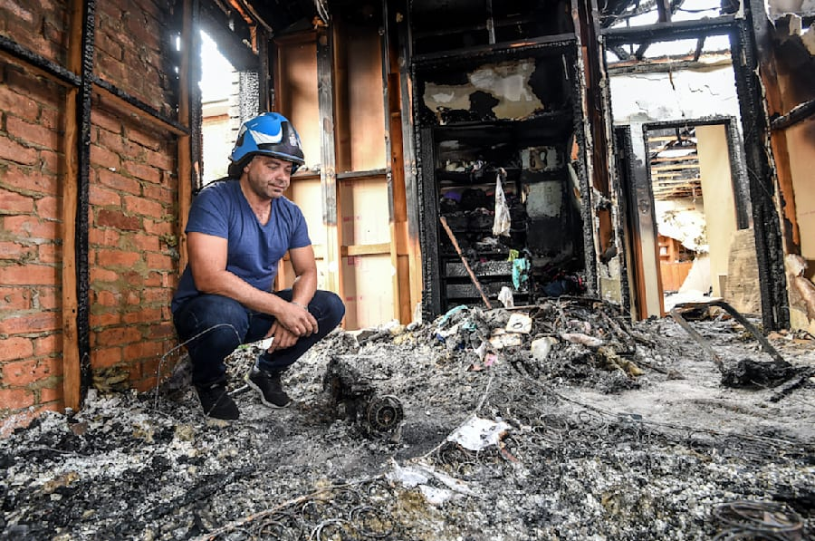 Ash Ibraheim with a burnt out hoverboard in his daughter's bedroom in Strathmore, following a