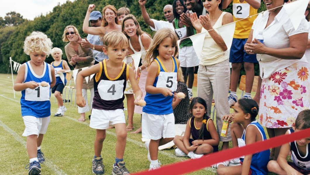 Children (4-6) running to finish line in egg and spoon race