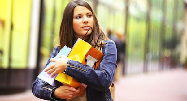 Young woman holding shopping bags in arms