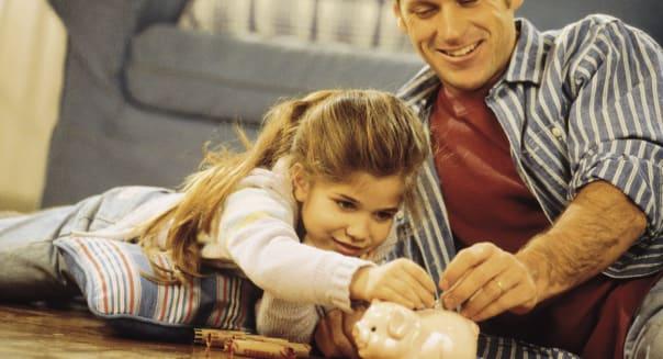 Father and daughter putting money into piggybank