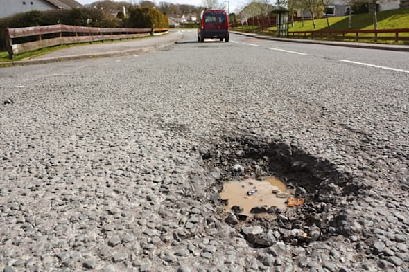 Large deep pothole an example of poor road maintance due to reducing local council repair budgets