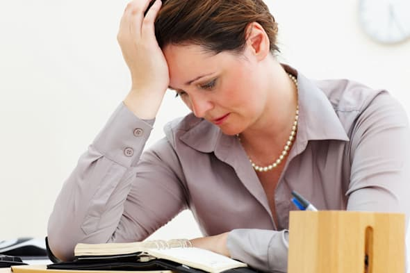C4PYYA Tensed middle aged business woman with hand on head reading a dairy