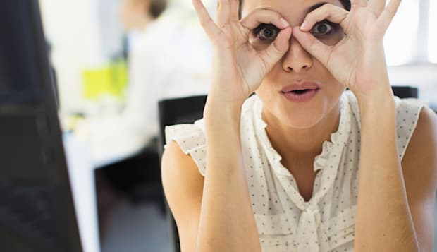 Businesswoman making a face at desk in office