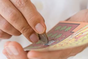 ANMT0Y Man scratching lottery card with coin