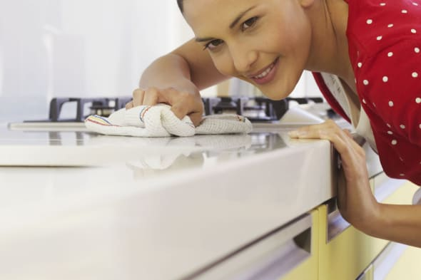 Young woman cleaning kitchen surface