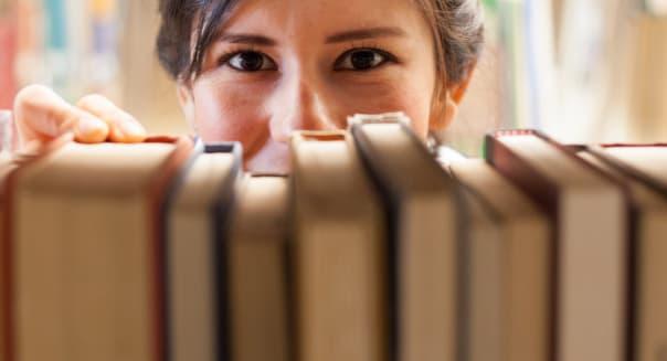 Close-up of woman grabbing book at bookstore.