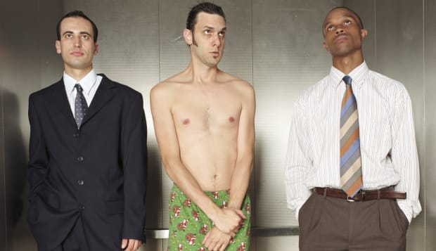 Businessmen in elevator, man wearing shorts