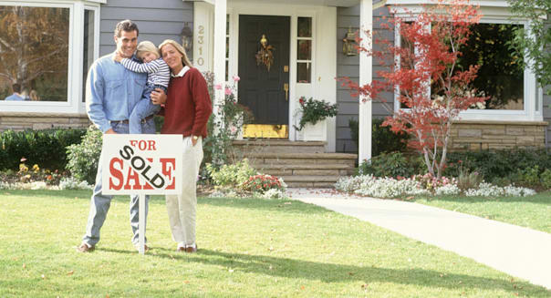 Family with For Sale sign outside of house