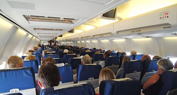 A68PNE Passengers on board holiday jet in flight seated three each side of gangway aisle