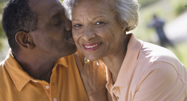 couple standing in park, man kissing wife on cheek, close-up