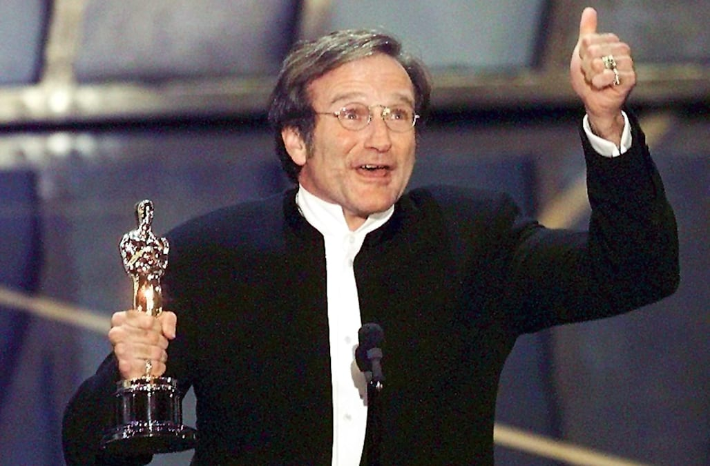 Actor Robin Williams holds up his Oscar after winn