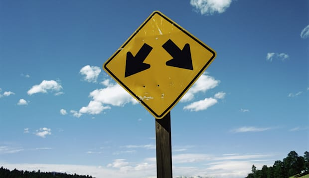 A road sign with two arrows pointing in different directions