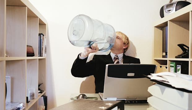 Businessman sitting at desk drinking from water cooler bottle
