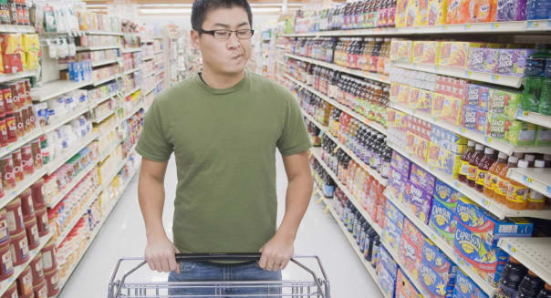 Young adult Asian male standing In aisle of grocery store looking confused while pushing cart and looking at selection of grocer