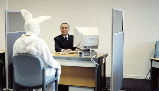Man wearing rabbit suit at desk opposite mature businessman