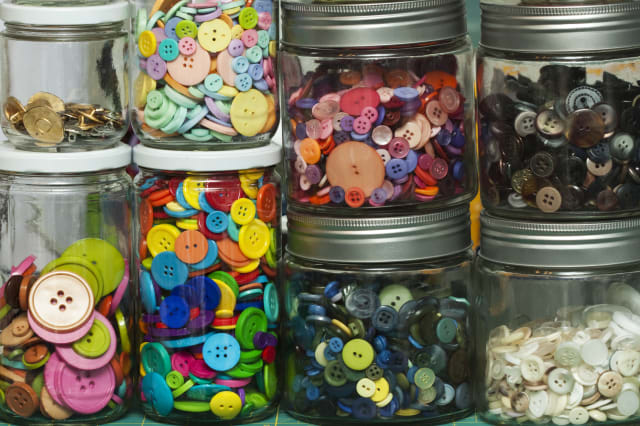 Neatly arranged jars display buttons sorted by color and category.