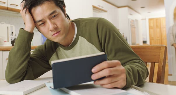 Man in kitchen looking at checkbook, resting on arm