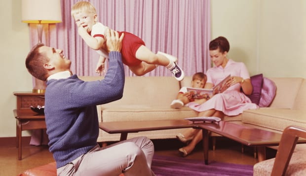 Parents relaxing with children in living room